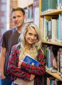 学生は図書館の本棚のそばに立って — ストック写真