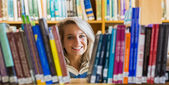 Smiling female student reading book in the library — Stock Photo