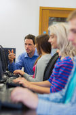 Teacher showing something on screen to student in computer room — Stock Photo