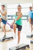 Инструктор с фитнес-класс, выполняющего Степ-аэробика упражнения — Стоковое фото