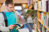 Two young students by bookshelf in the library — Stock Photo
