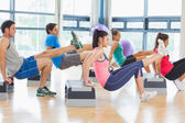 Instructor with fitness class performing step aerobics exercise — Foto de Stock