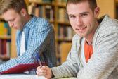 Retrato de un sonriente estudiante masculino en el mostrador de la biblioteca — Foto de Stock
