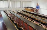 Elegancki mężczyzna nauczyciel siedzi w sali wykładowej — Zdjęcie stockowe