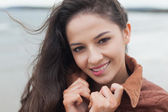 Cute smiling woman in stylish brown jacket on beach — Stock Photo