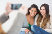 Woman photographing friends with smartphone — Stock Photo