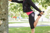 Side view of a woman stretching her leg during exercise at park — Stock Photo