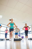Instructor with fitness class performing step aerobics exercise — Stock fotografie