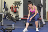 Healthy woman with an injured knee sitting in gym — Stock Photo