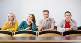 Thoughtful smiling college students in classroom — Stock Photo