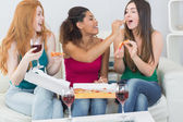 Happy female friends eating pizza with wine at home — Stock Photo