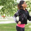 Side view of a beautiful healthy woman jogging in park — Stock Photo