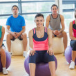 Smiling people sitting on exercise balls in the bright gym — Stock Photo