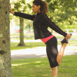 Healthy woman stretching her leg during exercise at park — Stock Photo
