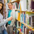 Two young students by bookshelf in the library — Stockfoto