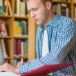 Young male student writing notes at library desk — Stock Photo #36250317