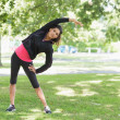 Full length of a healthy woman doing stretching exercise in park — Stock Photo