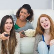 Cheerful friends with remote control and popcorn bowl at home — Stock Photo