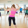 Fitness class and instructor swinging hula hoops at the waist — Stock Photo #36250613