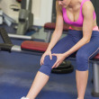 Healthy womwith injured knee sitting in gym — Stock Photo #36250675