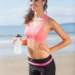 Beautiful smiling healthy woman holding water bottle on beach — Stock Photo #36250685