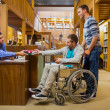 Stock Photo: Male student in wheelchair at library counter