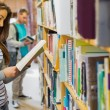 Two young students by bookshelf in the library — Foto Stock