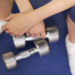 Low section of a tired woman with dumbbells in gym — Stock Photo #36251061