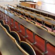 Empty seats with tables in a lecture hall — Stockfoto