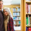 Young romantic couple with bookshelf at distance in library — Stok fotoğraf
