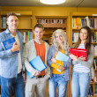 Students with folders against bookshelf in library — Stock Photo #36251289