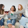 Cheerful female friends toasting wine glasses at home — Stock Photo