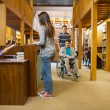 Stock Photo: Female student at library counter