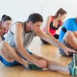 Stock Photo: Class and instructor stretching legs in exercise room