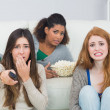 Photo: Scared friends with remote control and popcorn bowl at home