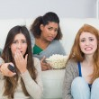 Scared friends with remote control and popcorn bowl at home — Stock Photo