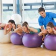 Stock Photo: Trainer helping womat fitness studio