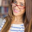 Close up of a smiling female student in library — Stock Photo
