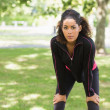 Tired young woman taking a break while jogging in park — Stok fotoğraf