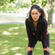 Tired young woman taking a break while jogging in park — Stock Photo
