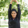 Healthy woman stretching her hands during exercise at park — Stock Photo