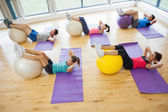 Class exercising with fitness balls at a bright gym — Stok fotoğraf