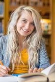 Porträtt av leende kvinnlig student vid biblioteket — Stockfoto