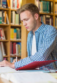 Young male student writing notes at library desk — Stock Photo