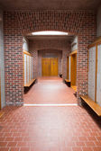 Empty brick walled corridor with tiled flooring in college — Stock Photo
