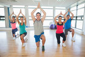 Fitness class and instructor kneeling in Namaste position — Stock Photo
