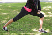 Low section of woman doing stretching exercise in park — Stock Photo