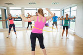Fitness class and instructor swinging hula hoops at the waist — Stock Photo