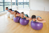 Fitness class exercising on fitness balls in a row — Zdjęcie stockowe