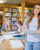 Female student with others in background at library — Stock Photo